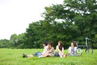芝に座り遠くを見る若者4人