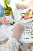 庭でワインをあける夫婦の手元 22964001142| 写真素材・ストックフォト・画像・イラスト素材|アマナイメージズ