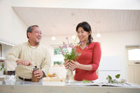 花を飾る妻とミルで豆を挽く夫