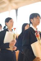 卒業証書と花を持った女子学生