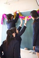 黒板に飾り付けする女子学生