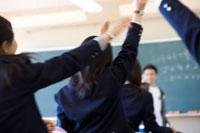 挙手する女子学生