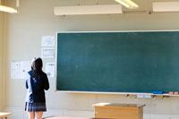 黒板の脇に立つ女子学生