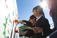 野外のボードに絵を描く女子学生