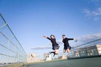 屋上で飛び上がる女子学生