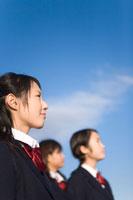前を見上げる女子学生と青い空
