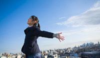 屋上で空に向かって両手を広げる女子学生
