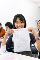 ゼミナールのテスト用紙を掲げる女子生徒