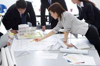 模型と図面で打合せをする会社員