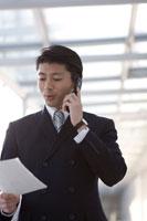 書類を手に携帯電話をかけるビジネスマン