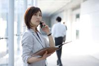 ファイルを広げて携帯電話をかける女性