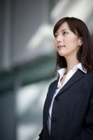 遠くを見つめる女性の会社員