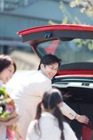 赤い車に荷物をつむ家族