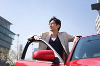 赤い車のドアに手をかけ遠くを見る男性