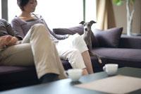 ソファーで寛ぐ男女と犬