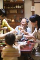 ビールを片手に笑顔の父親と土鍋を囲む家族