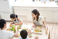 食卓で食事をする家族