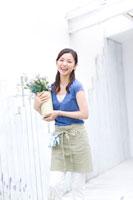 花を持ってたつ持つ女性