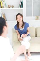 ソファに座る女性と会話する男性