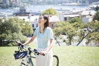 自転車を引いている女性 22980000091| 写真素材・ストックフォト・画像・イラスト素材|アマナイメージズ