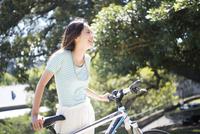 自転車の横で休んでいる女性 22980000095| 写真素材・ストックフォト・画像・イラスト素材|アマナイメージズ