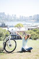自転車の横で休んでいる女性