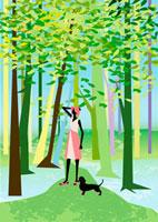 樹木の中で犬と散歩する女性
