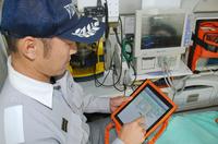 救急車内でiPadを操作し、急患の搬送先を検索する救急隊員