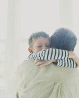 外国人の男の子が父の背中に抱きつく