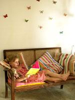 椅子で本を読んでいる外国人の女の子