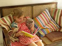 猫と本を読んでいる外国人の女の子