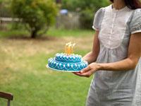 誕生日ケーキを持ってい来る外国人の母 24001000072| 写真素材・ストックフォト・画像・イラスト素材|アマナイメージズ