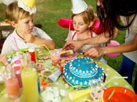 誕生日ケーキをカットする外国人の母