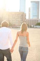 手をつないで街中を歩く男性と女性