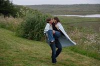 草原で女性を抱きかかえる男性