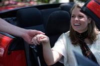 助手席の女性に手を差し伸べる男性