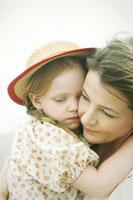 海岸で娘を抱っこする母