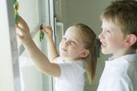 窓にシールを貼る男の子と女の子