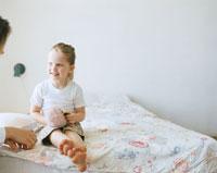 ベッドの上でぬいぐるみと遊ぶ女の子