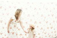 花柄背景の前で手をつなぐ母と娘