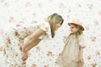 花柄背景の前で娘に話かける母 24003000044  写真素材・ストックフォト・画像・イラスト素材 アマナイメージズ