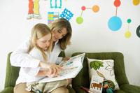 ソファーの上で娘に絵本を読む母
