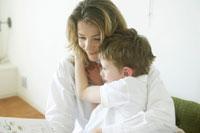絵本を読みながら息子を抱擁する母