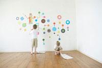 壁にシールを貼って遊ぶ男の子と女の子