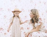 花柄背景の前で母の肩をつかむ娘 24003000113  写真素材・ストックフォト・画像・イラスト素材 アマナイメージズ