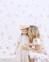 花柄背景の前で娘にささやく母 24003000115| 写真素材・ストックフォト・画像・イラスト素材|アマナイメージズ