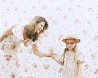 花柄背景の前で母の手をつなぐ娘