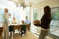 サンクスギビングディナーのターキーをテーブルに運ぶ母親 24003000123| 写真素材・ストックフォト・画像・イラスト素材|アマナイメージズ