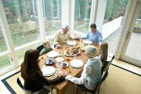 サンクスギビングディナーの前にお祈りをする家族 24003000124| 写真素材・ストックフォト・画像・イラスト素材|アマナイメージズ