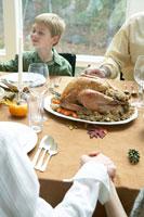 サンクスギビングディナーの前にお祈りをする家族 24003000126| 写真素材・ストックフォト・画像・イラスト素材|アマナイメージズ